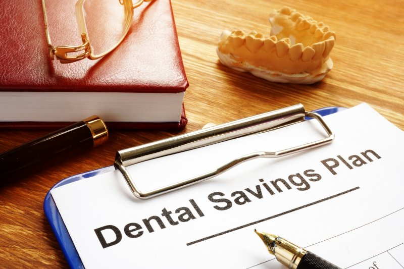 "a clipboard that reads ""Dental Savings Plan"" with a pen and other objects nearby"